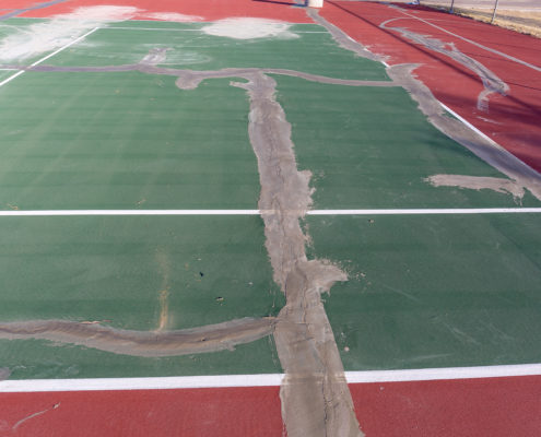 A tennis court with cracks being repaired with Armor Crack Repair in El Paso Texas